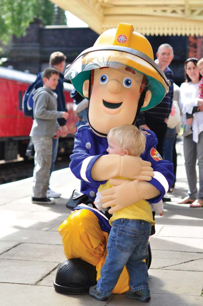 Fireman Sam mascot receives a hug from a young fan